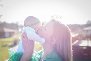 mother holding baby up in bright sunlight