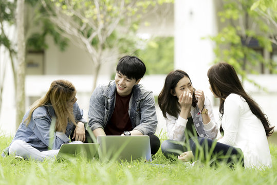 education, school and people concept - Cheerful university students with laptop on group of students in background at each other at school; Asia