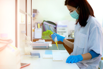 Young woman student as asia scientific researcher holding autopipette liquid solution in a laboratory.