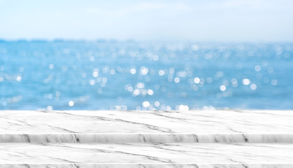 Empty white marble table top with blur blue sky and sea boekh background in sunny day,Mock up template for display or montage of product or content use as banner in social media ads