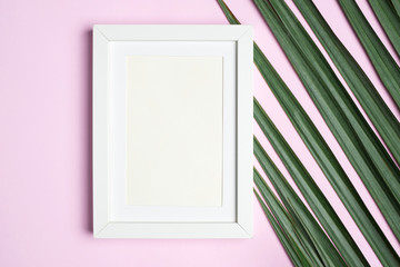Top view blank white photo frame on green palm leaf on pastel pink table top background.Summer vacation backdrop.Mock up for display design and text.
