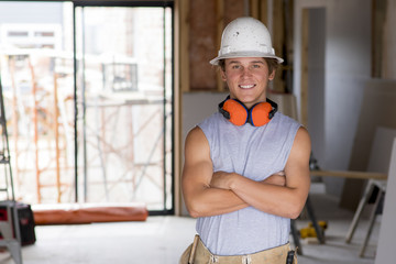 portrait of young attractive builder man on his 20s posing happy confident and proud at construction site wearing protection helmet