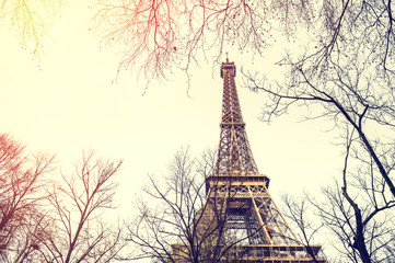 Eiffel Tower view through the trees in Paris, France. Vintage filter, retro effect