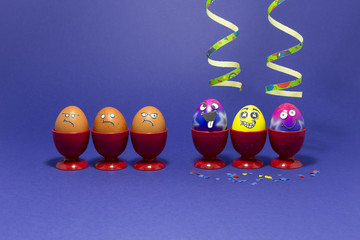 Group of colorful painted Easter eggs with funny cartoon style faces, confetti and paper streamers and group of grumpy looking brown eggs in red plastic egg cups on purple background
