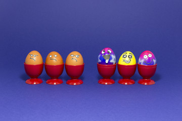 Group of colorful painted Easter eggs with funny cartoon style faces and group of grumpy looking brown eggs in red plastic egg cups on purple background