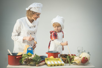 Mother teaches son to cook on light background.