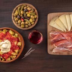 Tapas and wine. Patatas bravas, olives, jamon, cheese, square photo