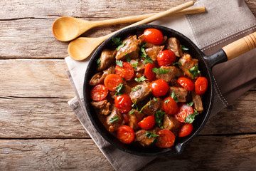 Veal in spicy sauce with cherry tomatoes and greens close-up in a pan. horizontal top view