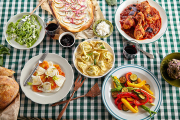 Traditional italian tuscan family dinner with homemade pasta and chicken cacciatore, focaccia and salad served on a table covered with green checkered tablecloth