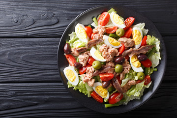 Delicious gourmet nicoise salad with vegetables, eggs, tuna and anchovies close up on a plate. Horizontal top view