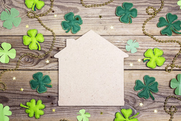 Lucky home symbol with four-leaf clover on wooden background. Copy space.