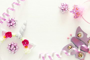 girl's party concept. unicorn head decoration, pink wand and toy over white wooden background.
