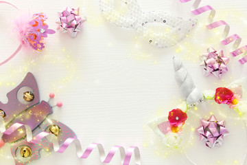 girl's party concept. unicorn head decoration, pink wand, mask and toy over white wooden background.