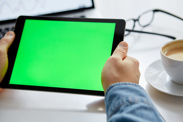 The man's hands with tablet with green chroma key. Work from Home on a Tablet