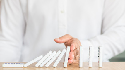 Stoping domino effect concept for business solution strategy and successful intervention with corporate person's hand blocking the collapse disruption