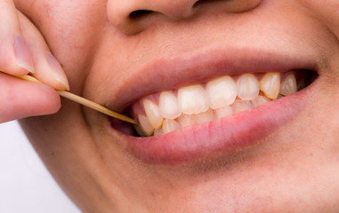 Asian woman clean her teeth from food stuck her teeth with bamboo wood toothpick after breakfast, lunch, dinner. Personal dental care with Asian style. Dental health and bad breath problem concept.