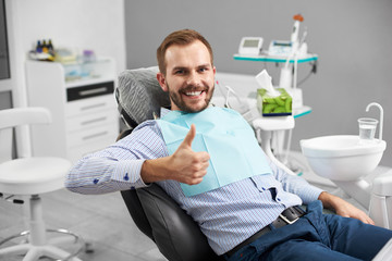 Portrait of happy patient in dental chair and shows a gesture with a thumb up class, good. Modern dentistry with the use of new technologies