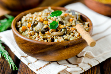 Buckwheat porridge with mushrooms in a wooden bowl