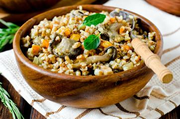Buckwheat porridge with mushrooms in a wooden bowl