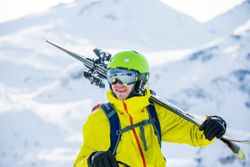 Portrait of sportive man in helmet with skis on his shoulder