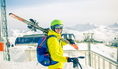 Image of sporty man in helmet with skis on his shoulder against background of snow-capped funicular