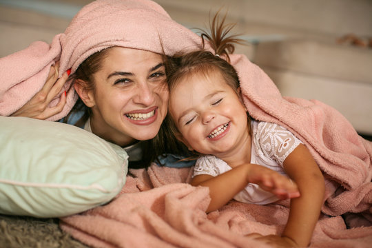 Mother and daughter playing together at home. Mother and daughter with blanket on head.