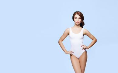 Fit and sporty girl in white underwear. Beautiful and healthy woman posing in swimsuit.