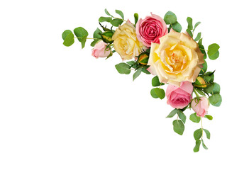 Pink and yellow rose flowers with eucalyptus leaves in a corner arrangement