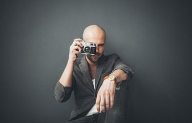 A bald man taking photos indoors enjoying