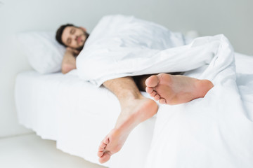 selective focus of man sleeping on bed, feet on foreground