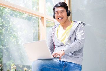 Portrait of Chinese young man wearing casual clothes while using a laptop in a modern office or at the university