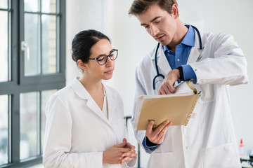 Two dedicated doctors checking together the information from the medical record of a patient in the interior of a modern hospital