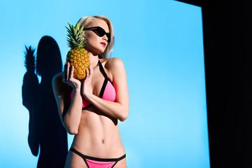 beautiful girl posing in bikini with pineapple for fashion shoot