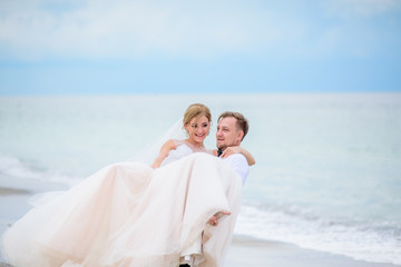 Groom holds bride on his hands standing on the beach with waves splashing behind them