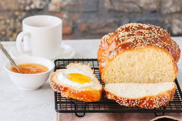 Homemade sesame seeds challah bread on a wire rack, orange jam and a cup of red tea on a white background.