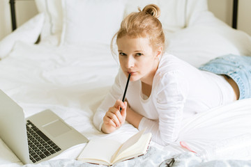 Young pretty woman working with laptop on the bed