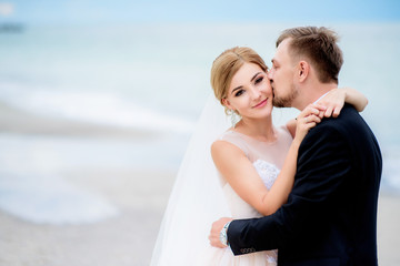 Dreamy wedding couple hug each other tender standing on the beach with sea waves splashing behind them