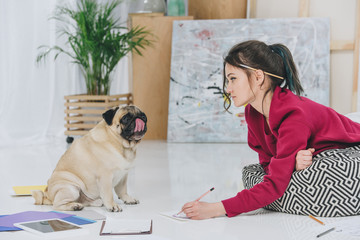 Pretty lady working on illustration and looking at cute pug dog