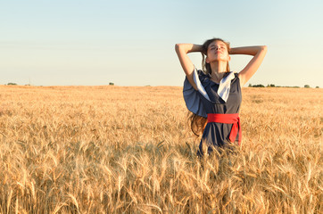 A beautiful young woman threw her hands up the hill  in the field in the wheat.