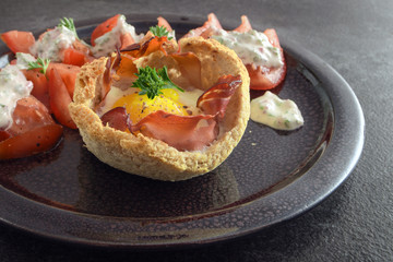 muffin from egg and bacon in toasted bread, tomatoes and cheese cream with herbs on a dark plate on rustic slate, creative breakfast, brunch or snack