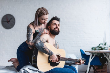 tattooed boyfriend playing guitar for girlfriend at home
