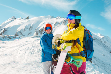 Photo of sportive man and woman with snowboard against background of snowy hills