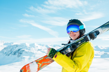 Picture of sports woman in helmet with skis on her shoulder against background of winter hills