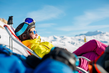 Image of smiling sportswoman lying on winter deckchair