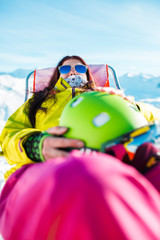 Portrait of sports long-haired brunette with helmet resting on chair in winter resort