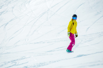 Image of woman wearing helmet in sports clothes snowboarding