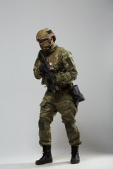Full-length image of military man in camouflage with gun