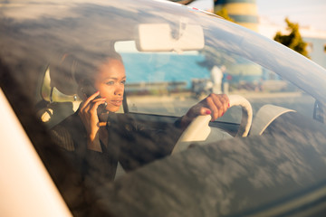 Young businesswoman talking on the phone in car