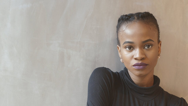 Serious attractive african woman with purple lipstick is looking in camera at isolated background.