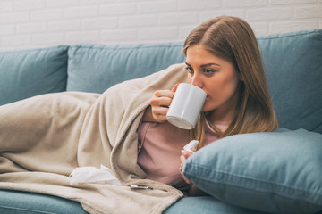 Exhausted woman having fever and she is drinking a tea.